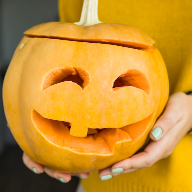 A festive pumpkin with eyes carved and a mouth with a candle inside Premium Photo