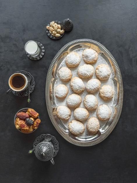 お祝いのラマダンのお菓子は、黒いテーブルでお茶と一緒にお召し上がりいただけます。エジプトのクッキー「カフエルイード」-エルフィトルイスラムのeast宴のクッキー。上面図 Premium写真