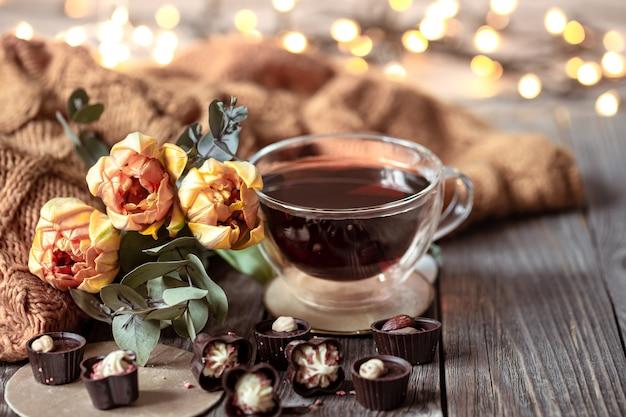 カップに入った飲み物、ボケ味のあるぼやけた背景にチョコレートと花のあるお祭りの静物。 無料写真
