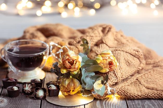 カップに入った飲み物、ボケ味のあるぼやけたテーブルの上にチョコレートと花があるお祭りの静物。 無料写真