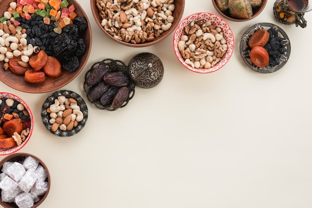 Festive still life with oriental ramadan dried fruits; nuts; dates and lukum on white background Free Photo