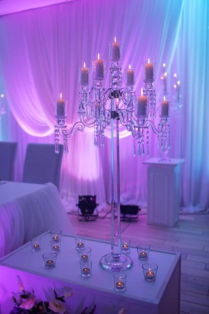 Праздничный стол украшен композицией из свечей и серебряных подсвечников в цветном свете в банкетном зале. стол молодоженов в банкетной зоне на свадебной вечеринке. Premium Фотографии