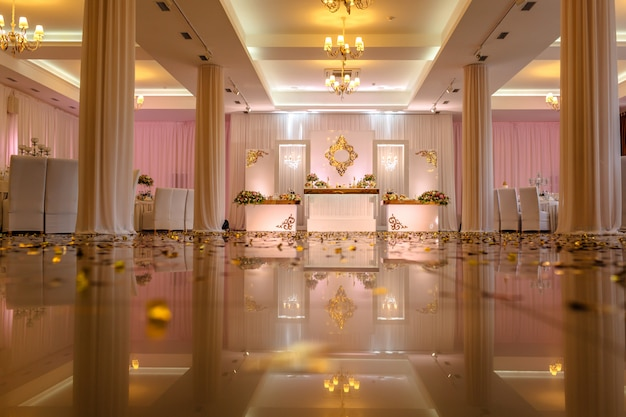 Festive table decorated with composition of white, red and pink flowers and greenery in the banquet hall. Premium Photo