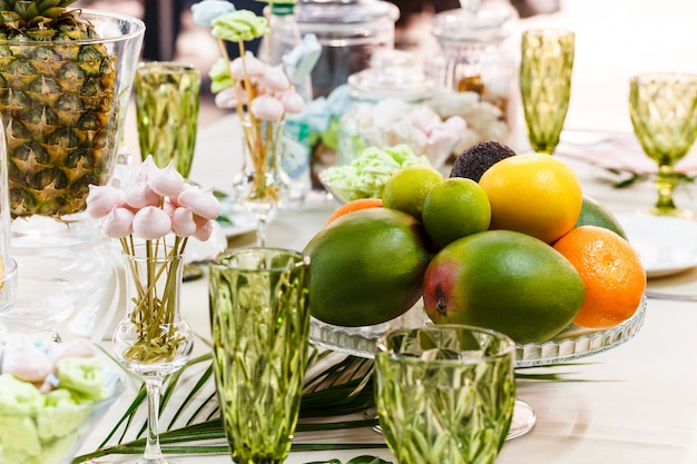 Festive table, decorated with vases, fruits and pastries. Premium Photo