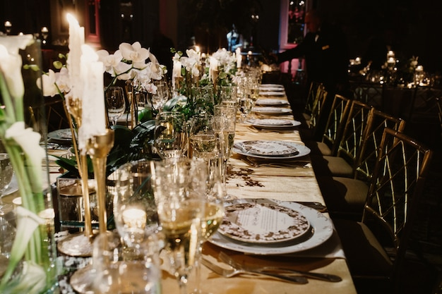 The festive table at the restaurant is decorated with candles and flowers Free Photo