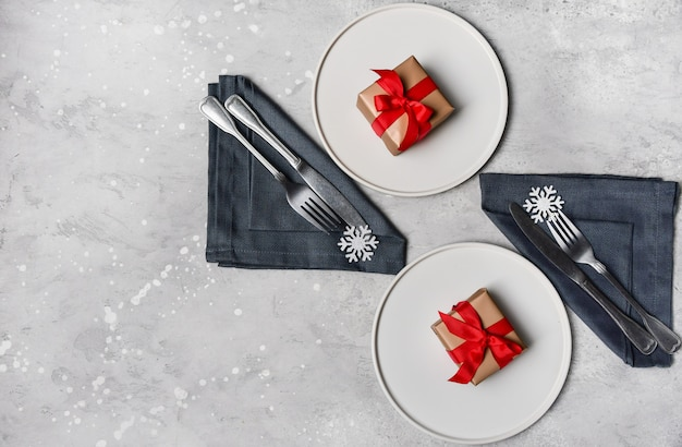 Festive table setting, christmas dinner  lunch. white craft plate, snowflake decor and gift  on stone table Premium Photo