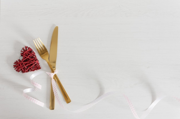 Festive table setting for valentine's day with golden fork and knife and decorations. Premium Photo