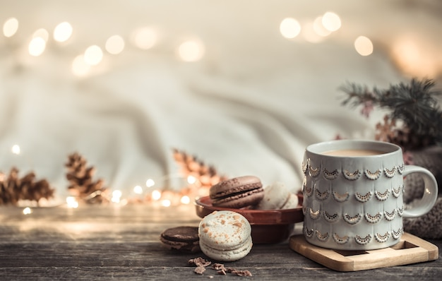 Festive wall with cup and dessert of macaroon. Free Photo