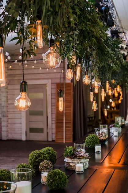 녹색 꽃 가지로 장식 끈에 매달려 갈 랜드의 에디슨 전구 축제 웨딩 테이블. 거친 효과 프리미엄 사진