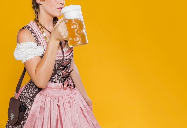 Festive woman in costume ready to drink beer Free Photo