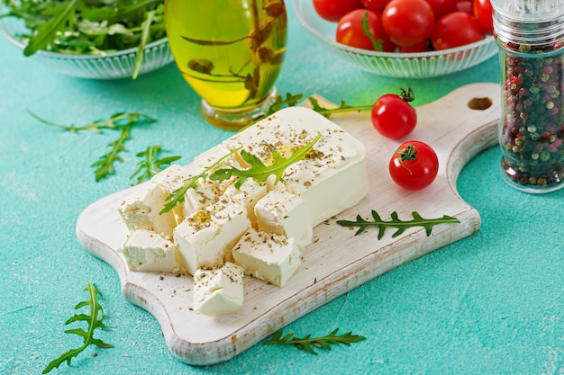 Feta cheese, cherry tomatoes and rucola on the table. ingredients for salad. Free Photo