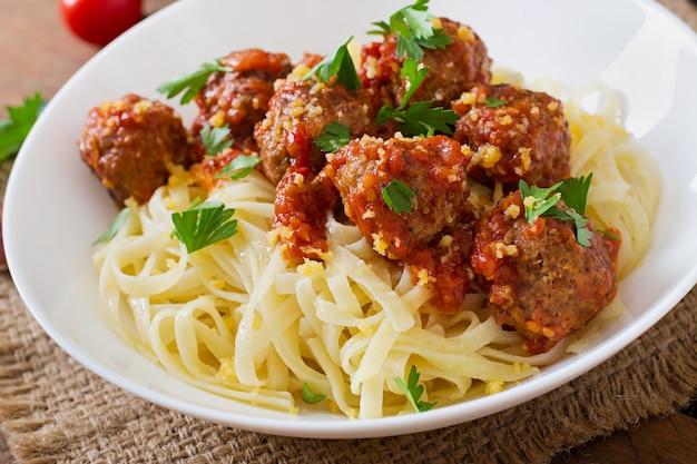 Fettuccine pasta with meatballs in tomato sauce Free Photo