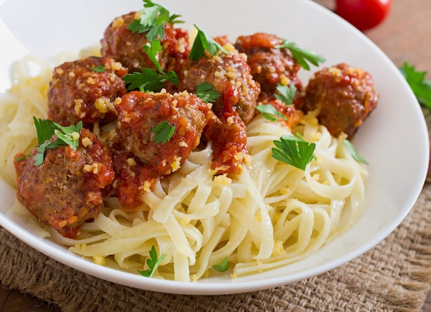 Fettuccine pasta with meatballs in tomato sauce Free Photo