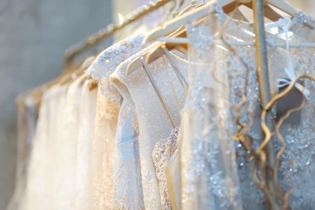 Few beautiful wedding dresses on a hanger. Premium Photo