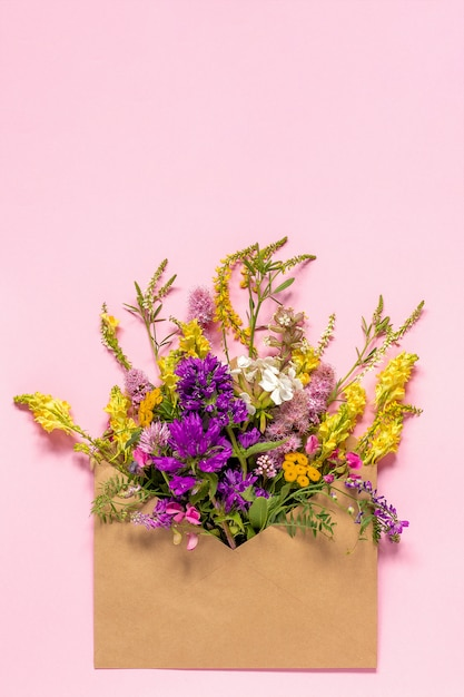 Field colorful rustic flowers in craft envelope on pink background greeting card concept hello spring Premium Photo