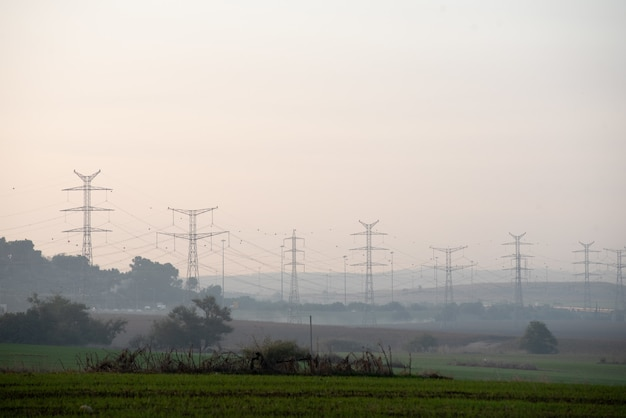 Campo ricoperto di vegetazione con torri di trasmissione sullo sfondo sfocato Foto Gratuite