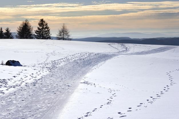Поле, покрытое снегом с холмами и зеленью на заднем плане во время заката Бесплатные Фотографии