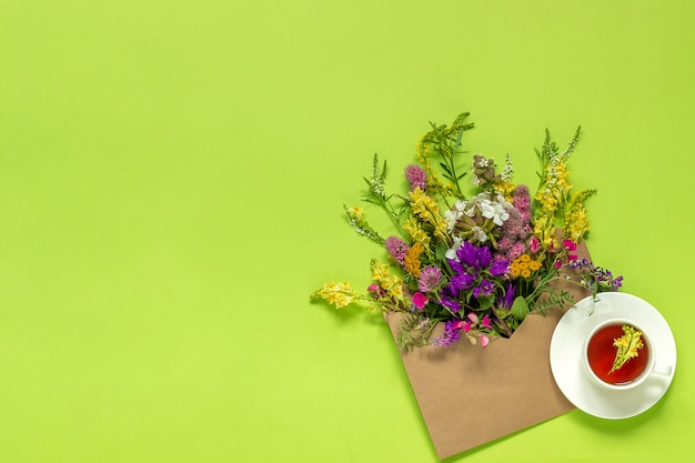 Field flowers in craft envelope and cup of herbs tea Premium Photo