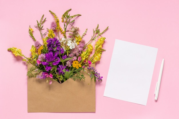 Field flowers in craft envelope and white empty paper card Premium Photo