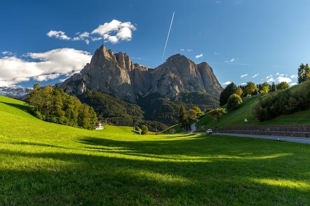 青い空とイタリアの日光の下で緑に覆われた岩に囲まれたフィールド 無料写真