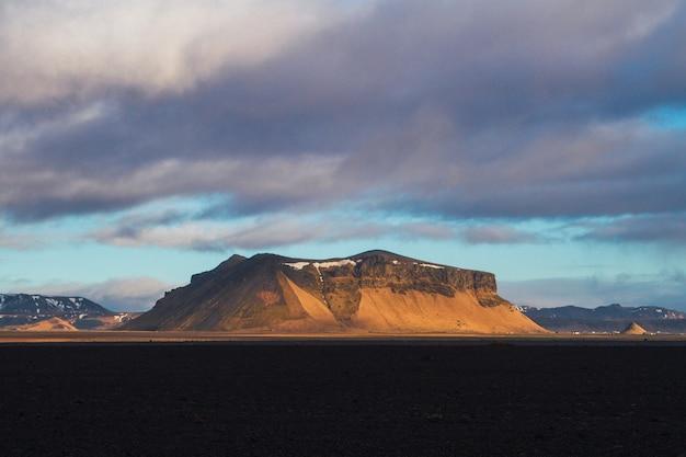 아이슬란드에서 일몰 동안 흐린 하늘 아래 눈으로 덮여 바위로 둘러싸인 필드 무료 사진