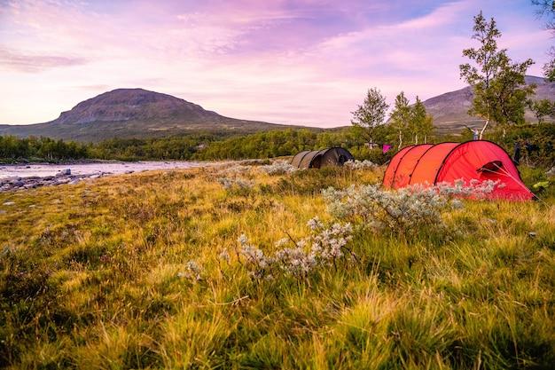 Поле с палатками в окружении холмов, покрытых зеленью, под пасмурным небом во время заката Бесплатные Фотографии