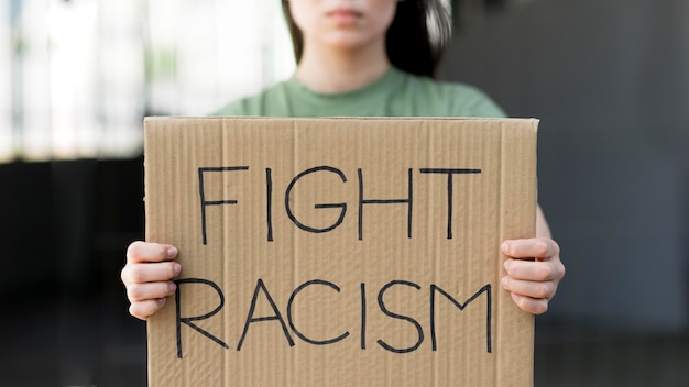 Fight racism quote on cardboard Free Photo