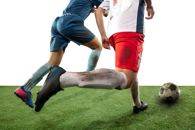 Боевые действия. закройте ноги профессионального футбола, футболистов, борющихся за мяч на поле, изолированном на белой стене. концепция действия, движения, сильных эмоций во время игры. обрезанное изображение. Бесплатные Фотографии