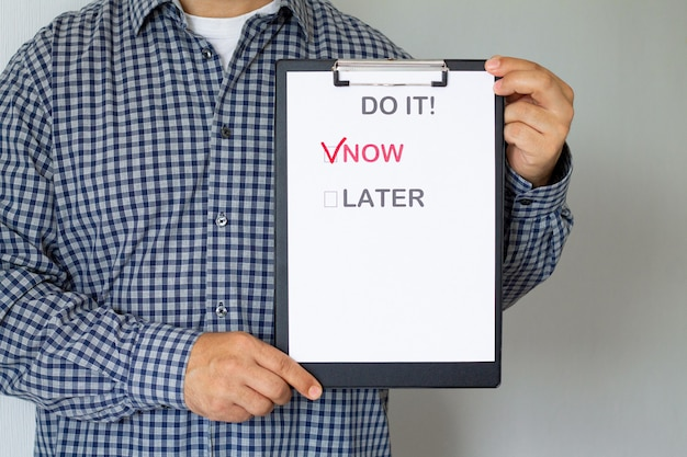 Fighting procrastination and business concept. man holding paper poster with text