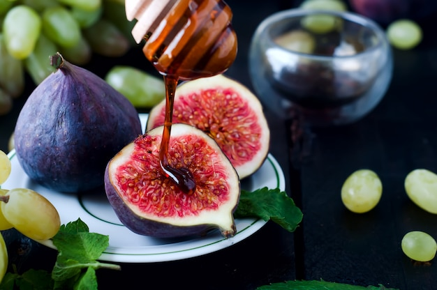 Figs and honey on wooden table background. Premium Photo