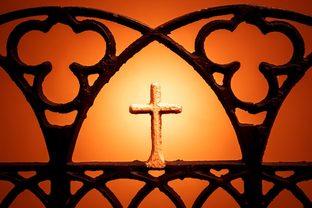 Figure of a cross on an orange background. christian cross silhouette. Premium Photo