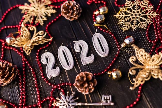 Фигурка нового года из красного ожерелья. еловые ветки на деревянных досках, вид сверху. рождественские украшения на деревянных фоне. копировать пространство Бесплатные Фотографии