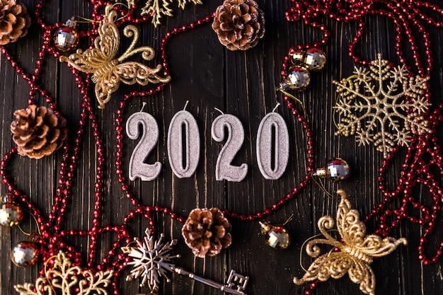 赤いネックレスからの新年の姿。木の板のトウヒの枝、上面図。木製の背景にクリスマスの装飾。コピースペース 無料写真