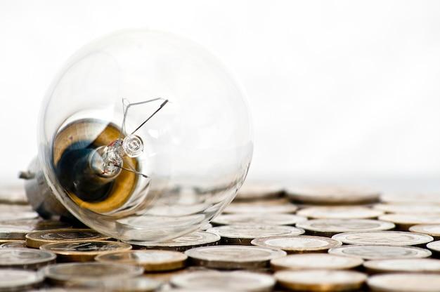 Лампа накаливания, лежащая на монетах евро Бесплатные Фотографии