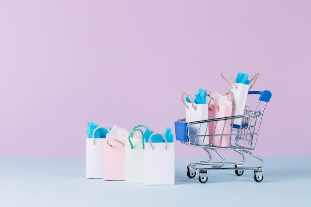 Filled miniature cart with paper shopping bags in front of pink background Free Photo