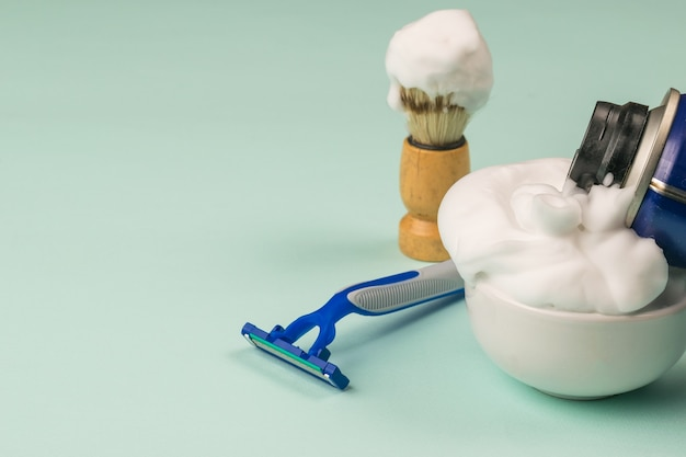 Filling the bowl with shaving foam and shaving accessories Premium Photo
