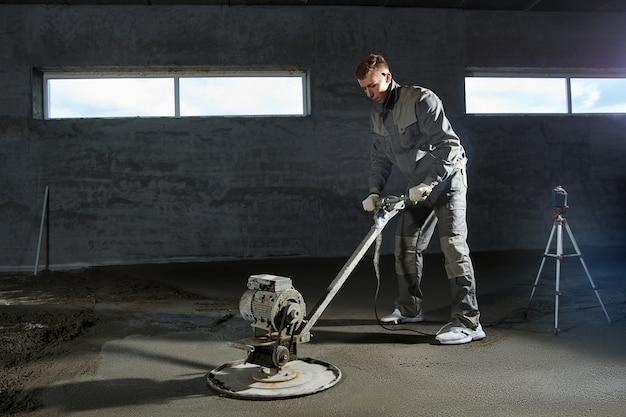 Заливка пола бетоном, стяжка и выравнивание пола строителями. ровные полы из цементной смеси, промышленное бетонирование. Premium Фотографии