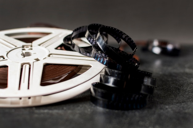 Film reel and film strips on dark background Free Photo
