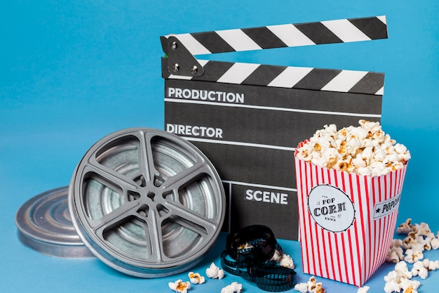 Film reels; film strips and clapperboard with popcorn box on blue background Free Photo