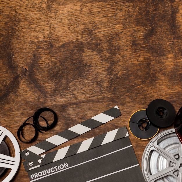 Film stripes; film reel and clapperboard on wooden desk Free Photo