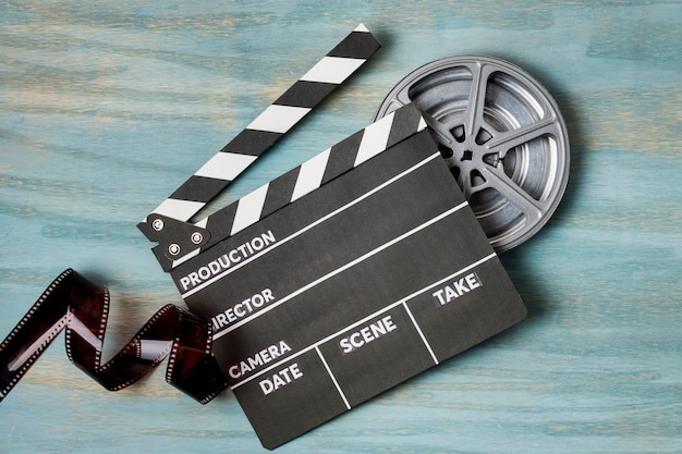 カチンコと青の織り目加工の背景にフィルムリールのフィルムストライプ Premium写真