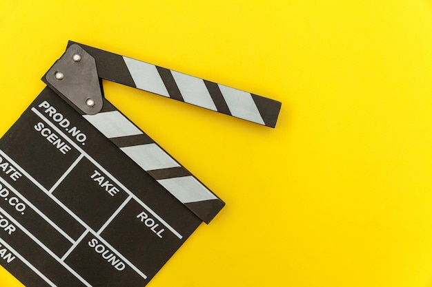 映画製作者の職業。古典的な監督の空の映画は、カチンコや映画のスレートを黄色の背景に分離します。ビデオ制作映画映画業界のコンセプト。フラットレイアウトトップビューコピースペースのモックアップ。 Premium写真