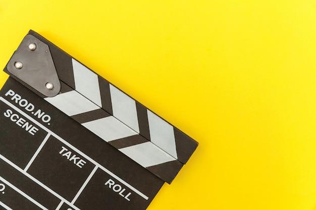 Кинопроизводитель по профессии. классический режиссер пустой фильм делает с 'хлопушкой' или фильм шифер, изолированные на желтом фоне. видео производство фильмов киноиндустрия концепции. плоские лежал вид сверху копией пространства макет. Premium Фотографии