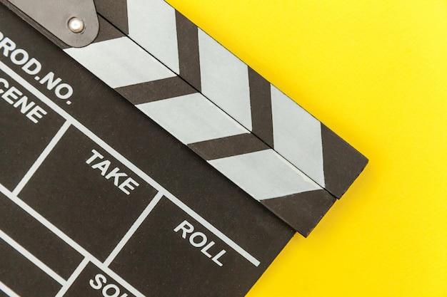 映画製作者の職業。古典的な監督の空の映画は、カチンコや映画のスレートを黄色に分離します。ビデオ制作映画映画業界のコンセプト。フラットレイアウトトップビューコピースペースのモックアップ。 Premium写真