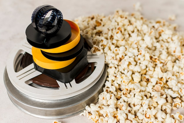 Filmstrip on yellow and black case over the movie film reel with popcorns Free Photo