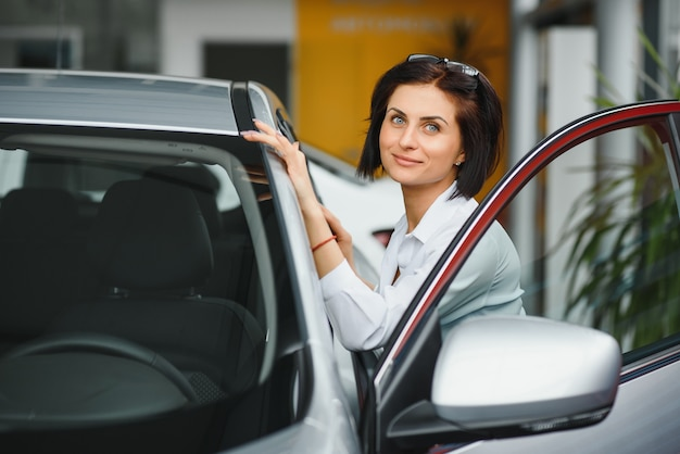 Finally new car! young female customer checking out a new car at the car dealership choosing buying decision purchase consumerism safety vehicle transport concept Premium Photo