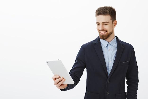 金融、ギグ経済、ビジネスコンセプト。自信に満ちた笑顔で満足するガジェット画面を見つめるデジタルタブレットを保持しているエレガントでスタイリッシュなスーツを着た自信を持って喜んで成功した男性起業家 無料写真