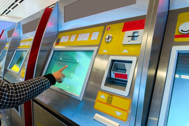 Finance, money, bank and people concept - close up of hand entering pin code at atm machine Premium Photo