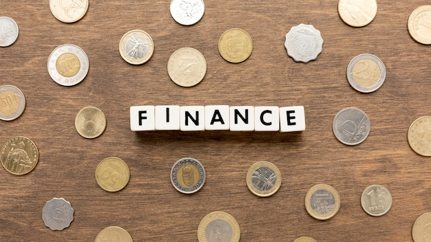 Finance word written in scrabble letters and coins Free Photo
