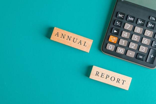 Концепция финансового учета с деревянными блоками, калькулятор на бирюзовом столе плоского положения. Бесплатные Фотографии